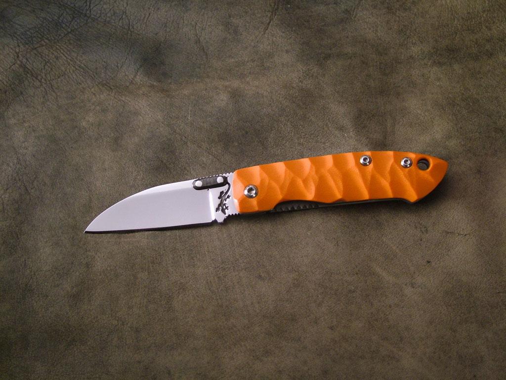 Frame-lock. Longueur fermé 9cm, lame 6cm. Acier 440C. Platines en acier Z20, côte en G10 orange toxifié.