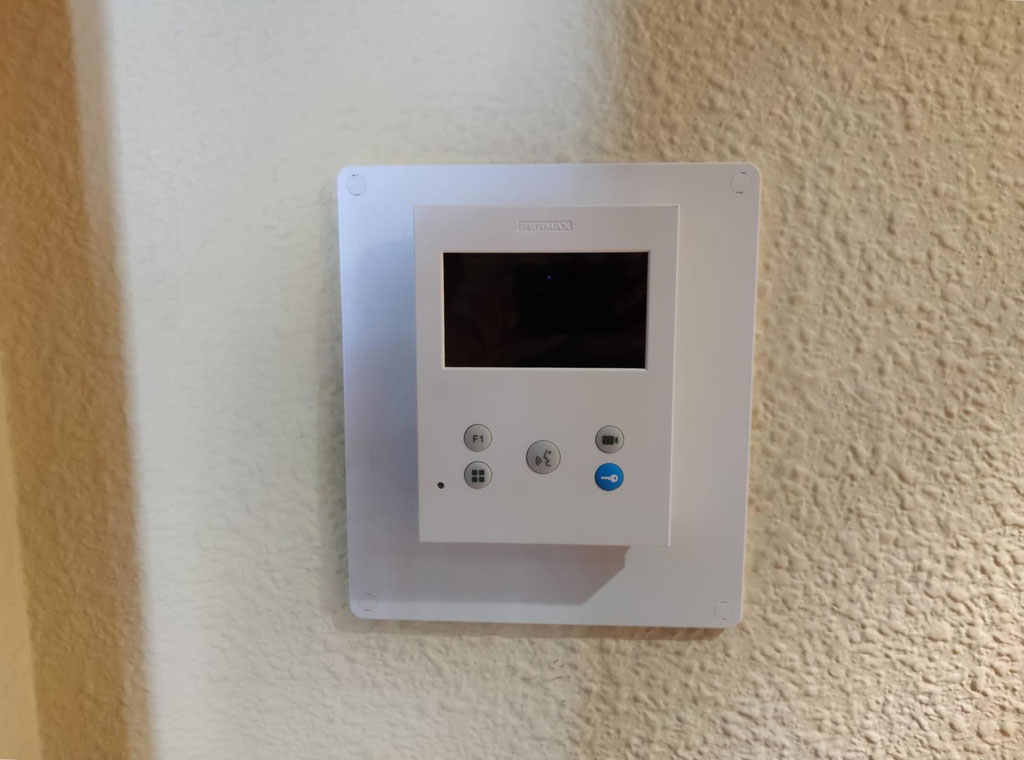 Detalle de monitor VEO DUOX PLUS de Fermax sobre pintura color beige con gotelé