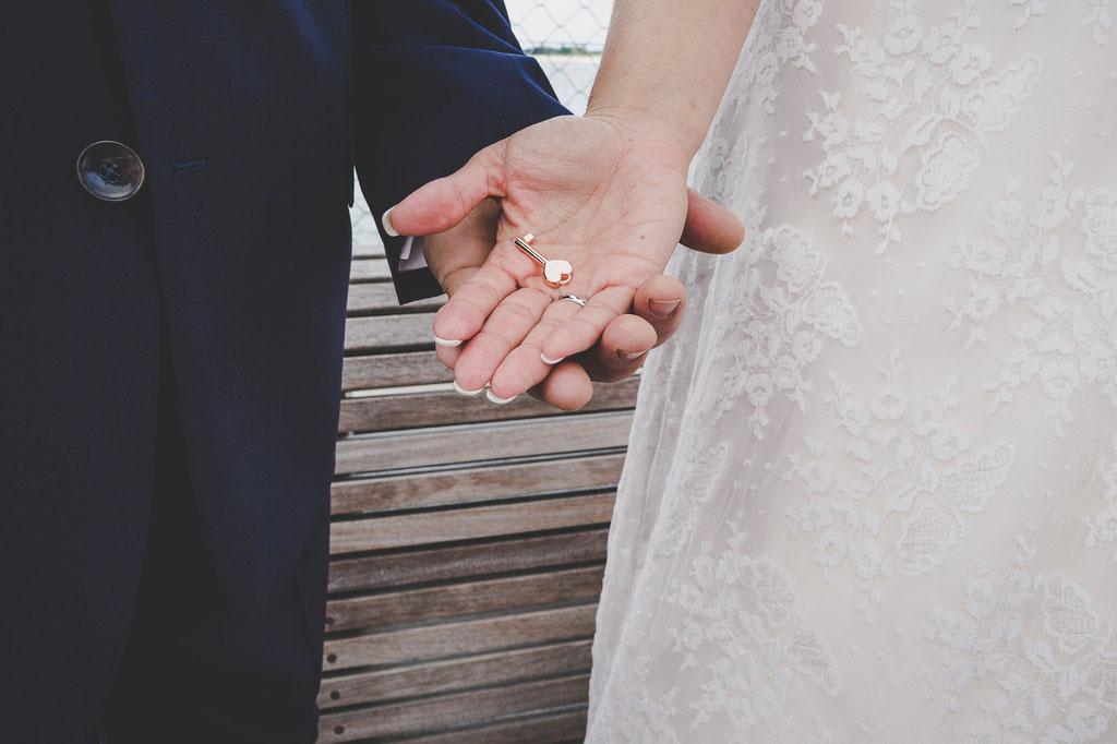 Herzschlüssel in der Hand von Braut und Bräutigam