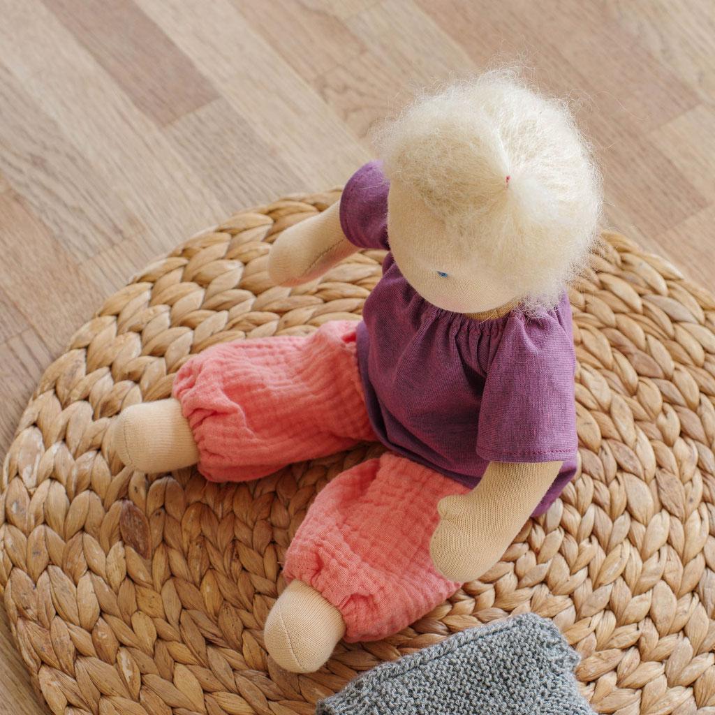 kleine Puppe handgemacht nach Vorbild der Waldorfpuppe sitzend mit lila Pullover und pinker Musslin Pumphose