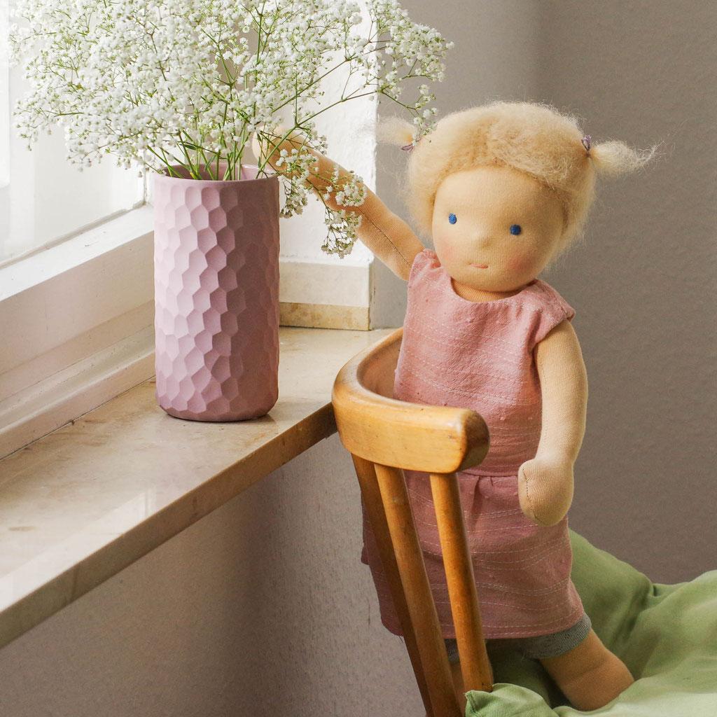 große Puppe nach Waldorfart mit blonden Haaren und Zöpfen steht auf einem Stuhl vor dem Fenster