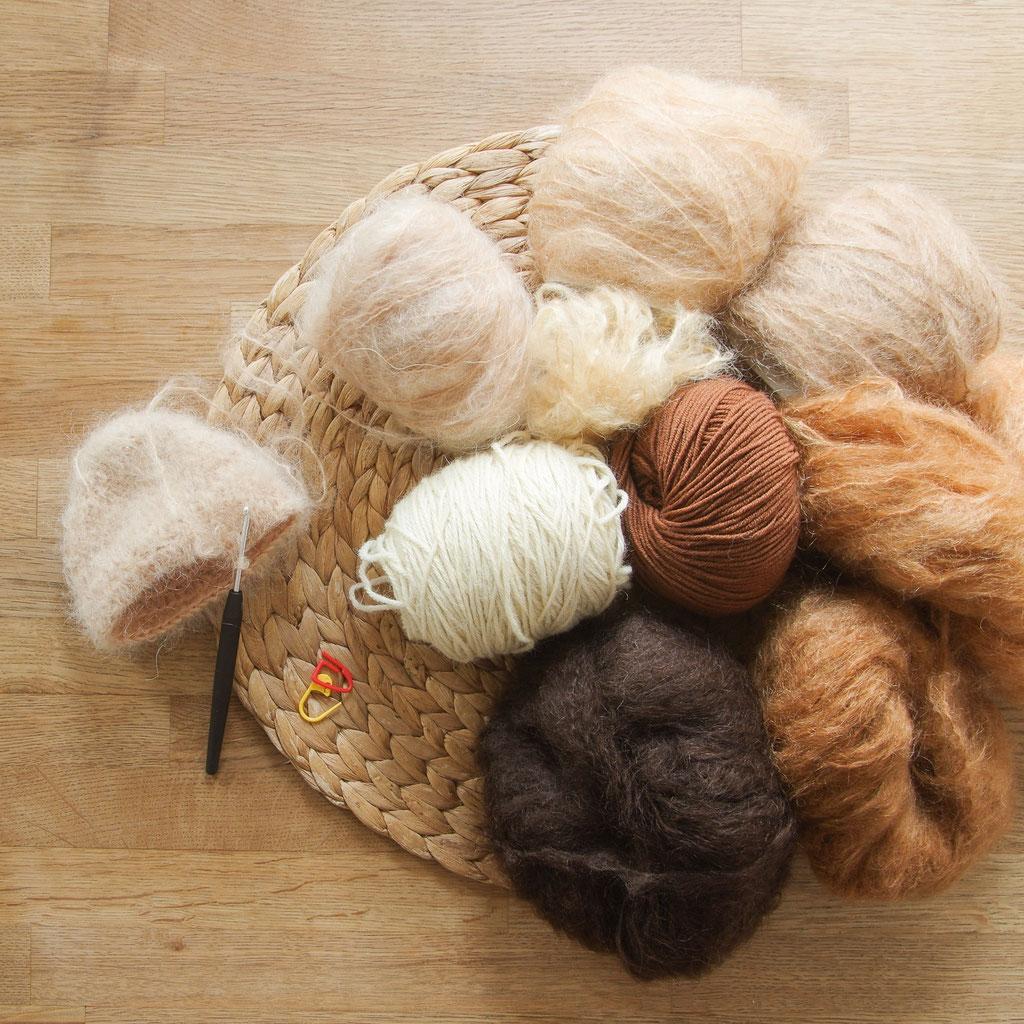 Mohair Wolle als Puppenhaar, zum häkeln einer Perücke, in blond, braun, kupfer liegt auf einem Holzuntergrund