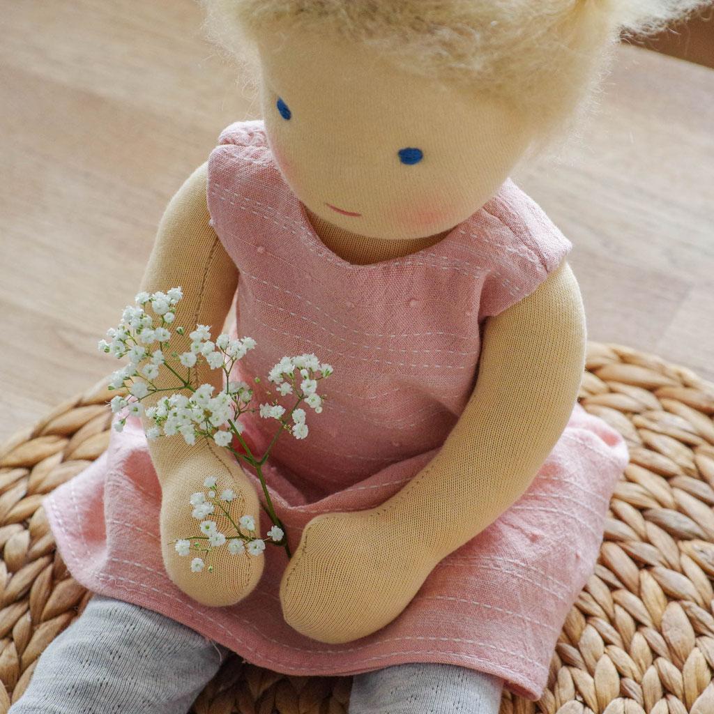 Puppe wie Waldorfpuppe 40 cm groß mit blonden Haaren und blauen Augen sitzt auf Holztisch mit Kleid und Leggins
