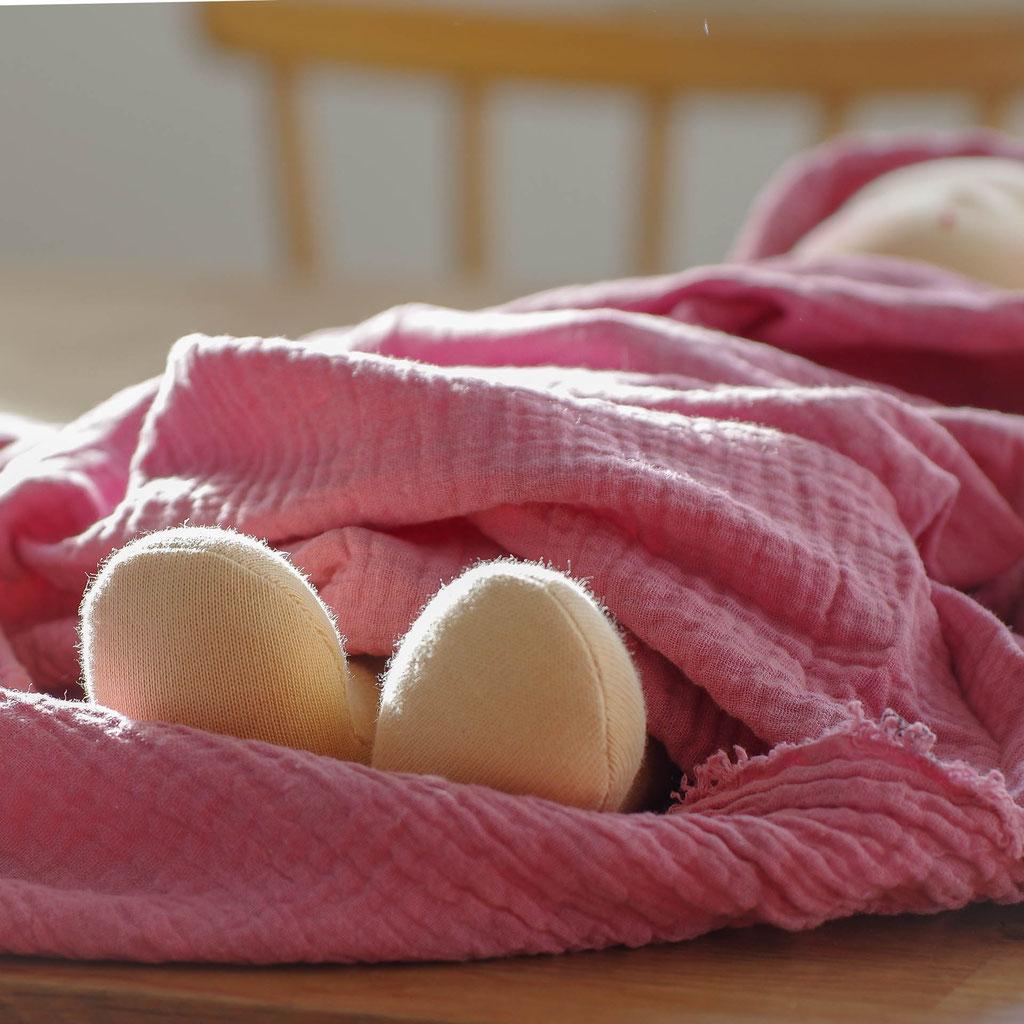 Handgemachte 40 cm große Stoffpuppe nach Art der Waldorfpuppe liegt wie Baby in Musselin Tuch auf dem Tisch