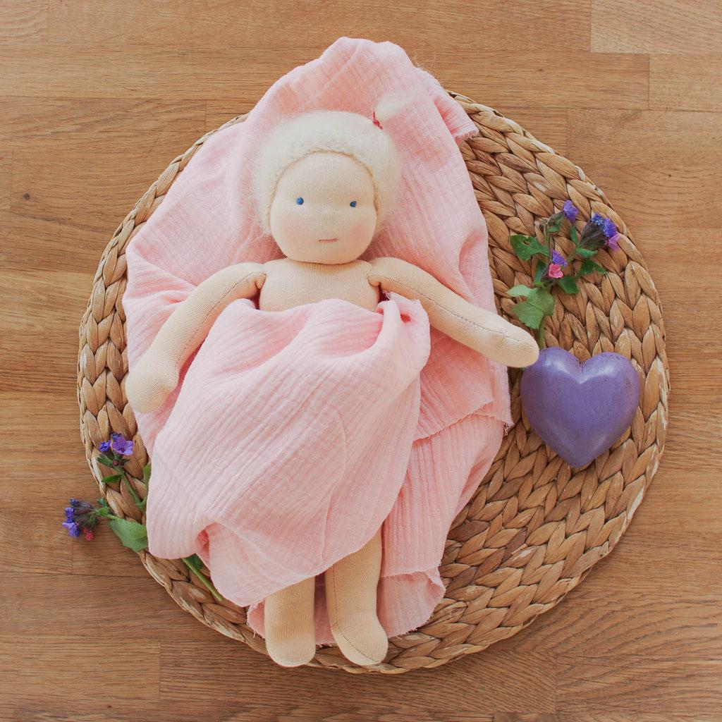 kleine Puppe nach Waldorfart liegt eingehüllt in ein rosa Musselintuch auf einem Holzuntergrund