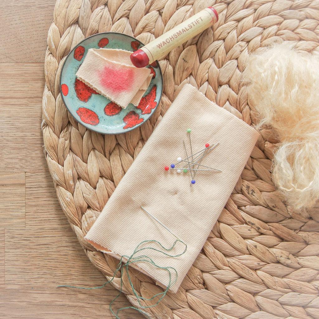 Puppentrikot, Puppenmohair, Stockmar Wachsmaler und Nadeln liegen auf einem Holzuntergrund