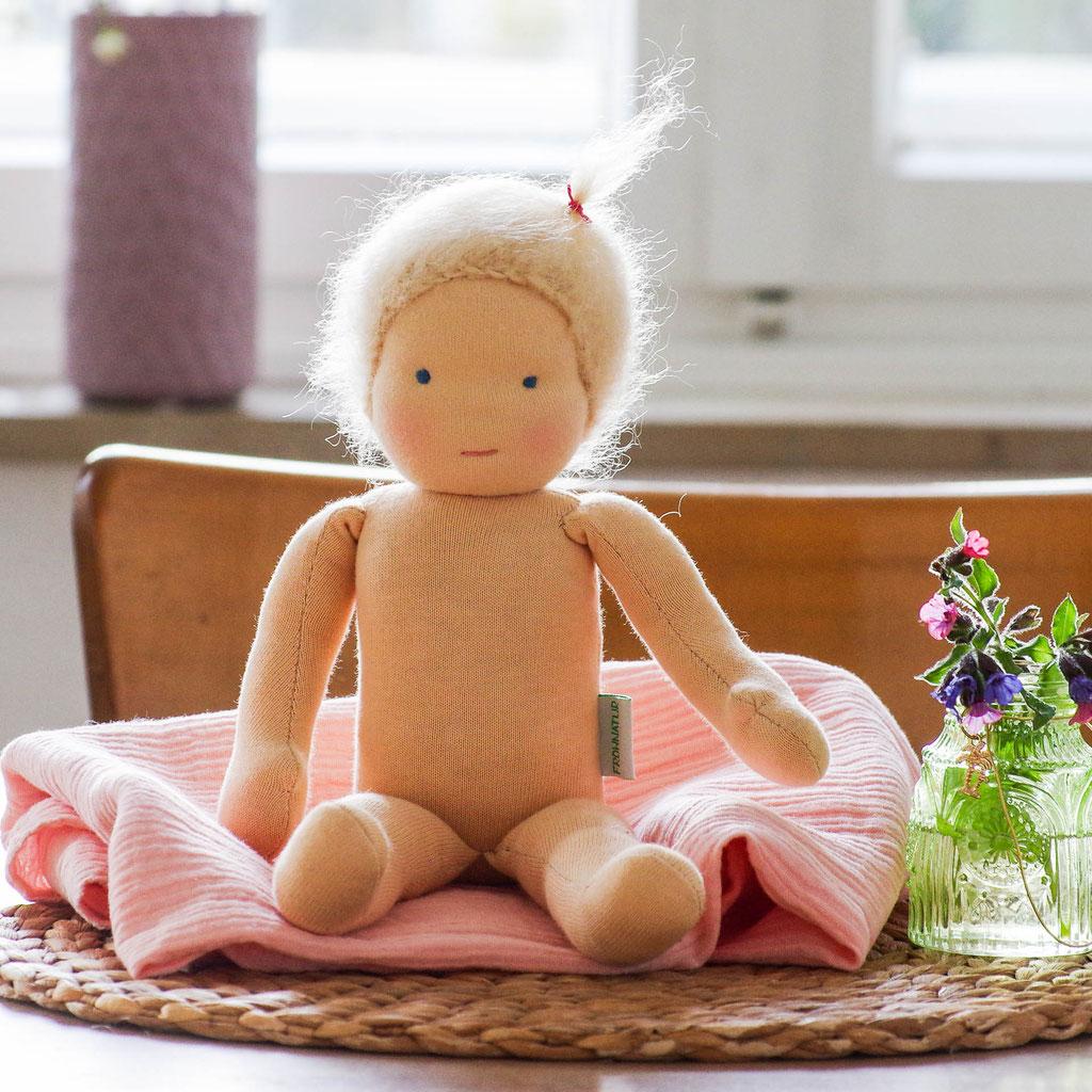 kleine Waldorfpuppe, blonde Frohnatur Puppe nach Art der Waldorfpuppe sitzt auf einem Holztisch