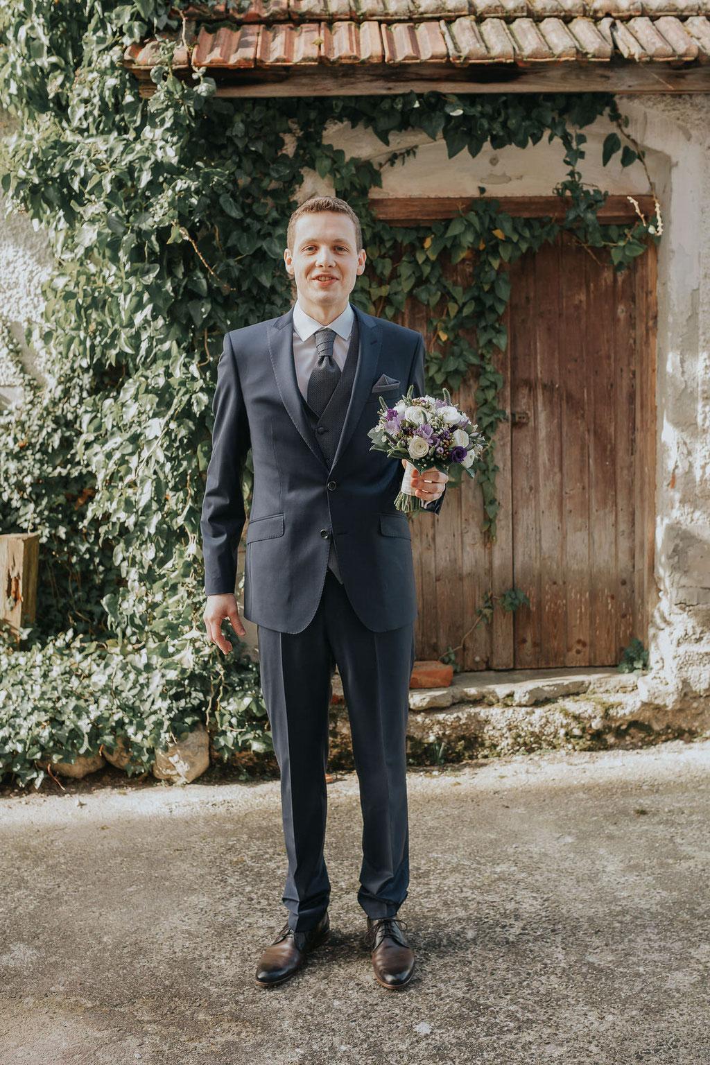 Bräutigam mit Blumen kurz bevor er seine Braut sieht