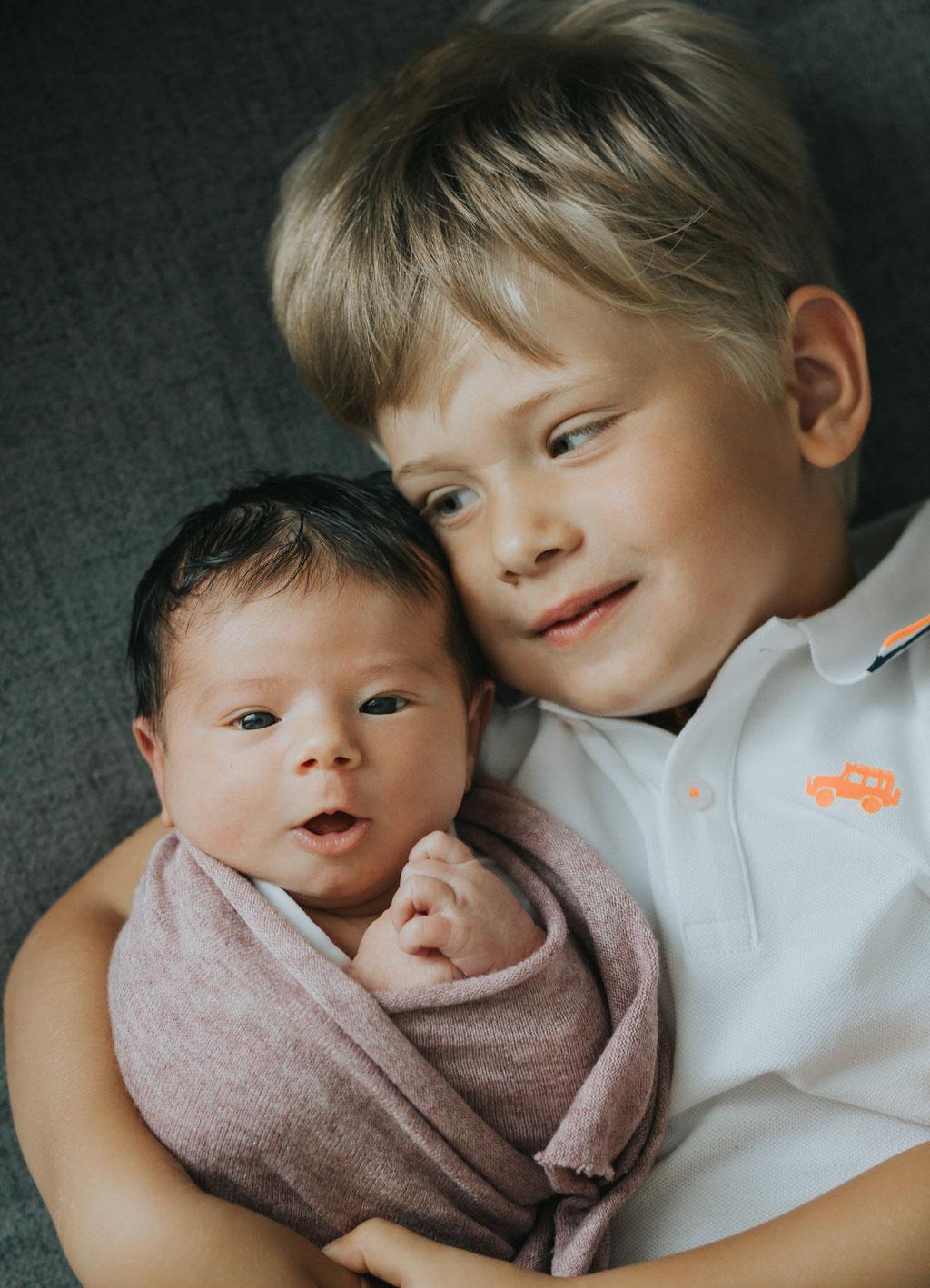 Neugeborenenfoto, Baby mit großem Bruder