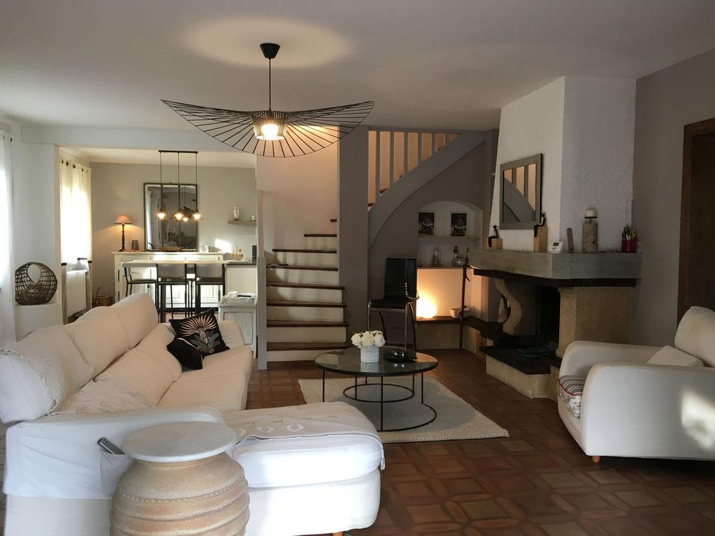 Ambiance sereine et naturelle pour ce grand séjour beige et blanc ouvert sur une cuisine et un escalier. canapé en lin blanc, suspension Vertigo Constance Guisset.