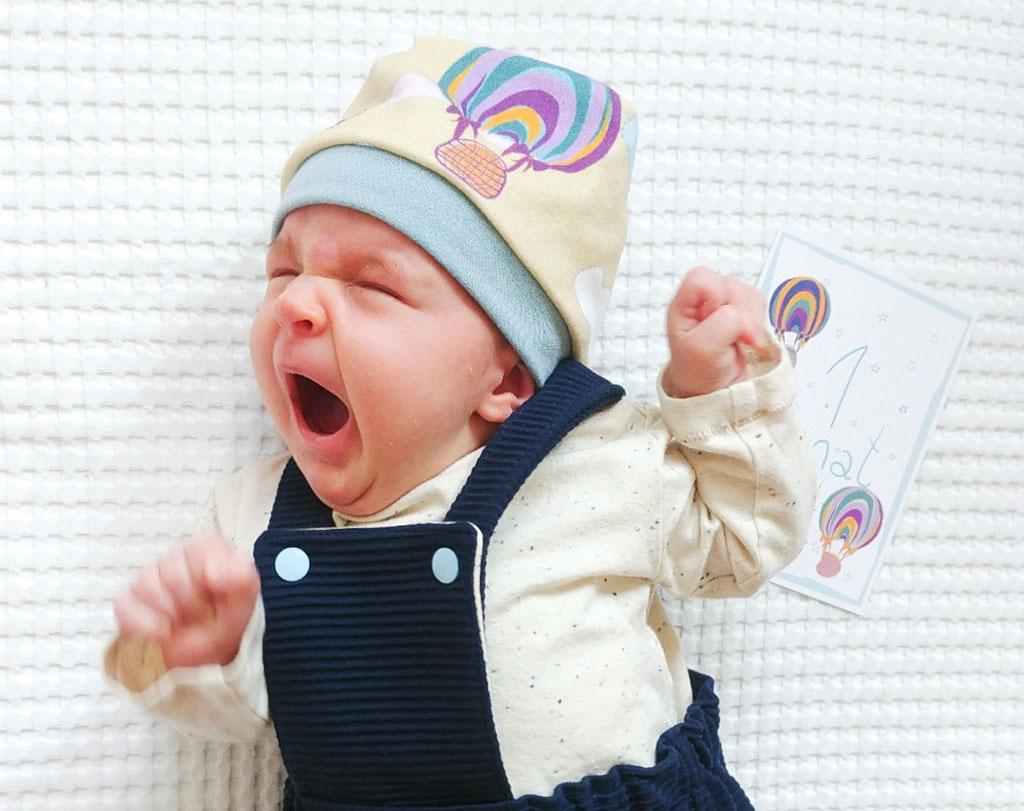 Baby mit Beanie Mütze und Latzkleid in Bio-Baumwolle