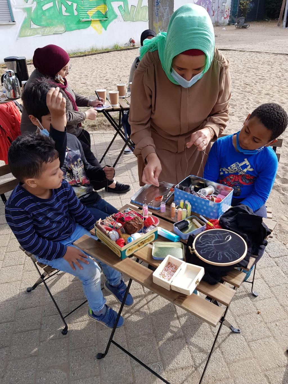Hallo Nachbar Frauencafé. Filiz Yildiz führt Handarbeiten vor. Die Jungen machen mit.