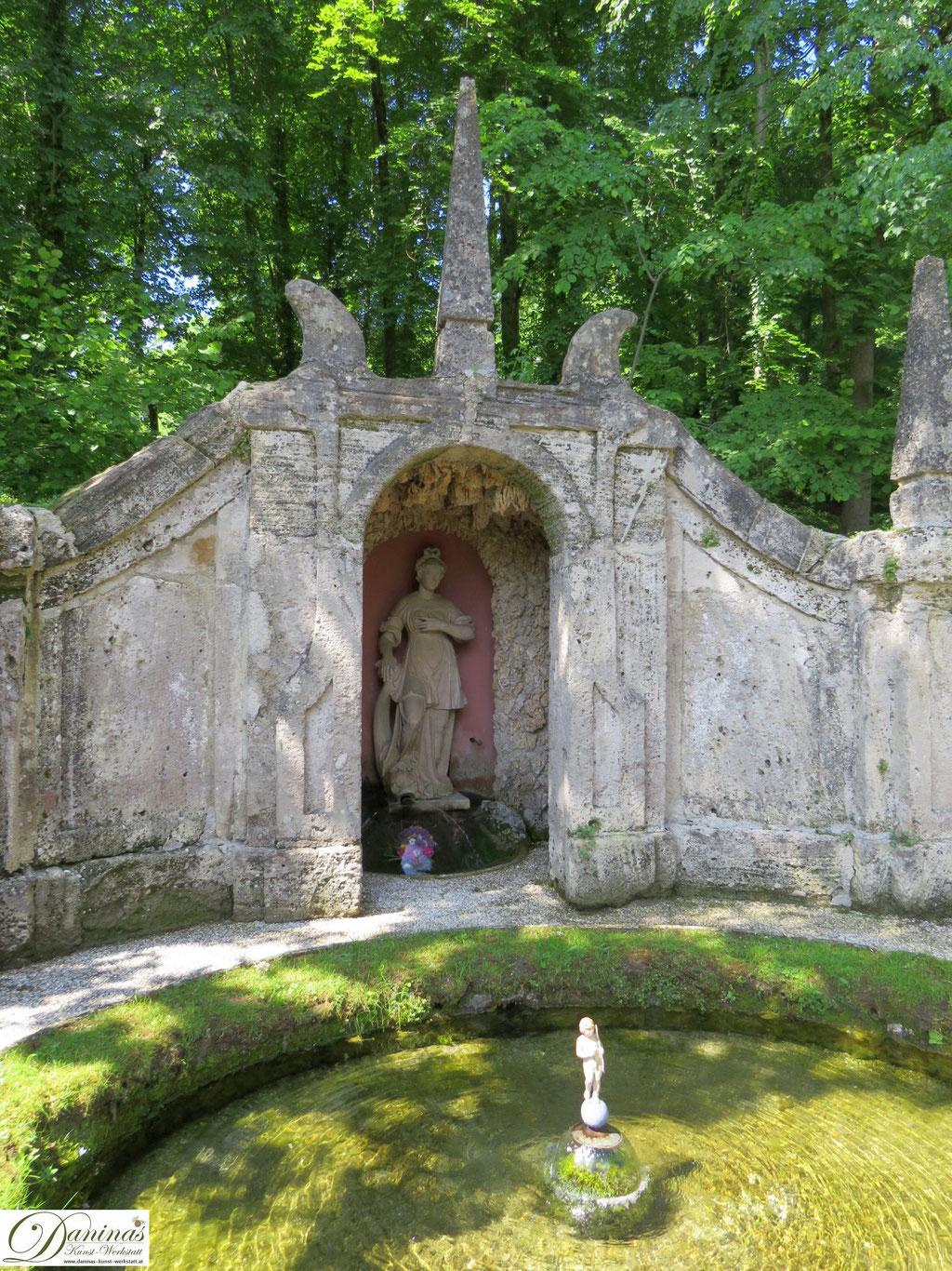 Venusgrotte, im Becken davor steht ein kleiner Amor - Hellbrunner Wasserspiele in Salzburg