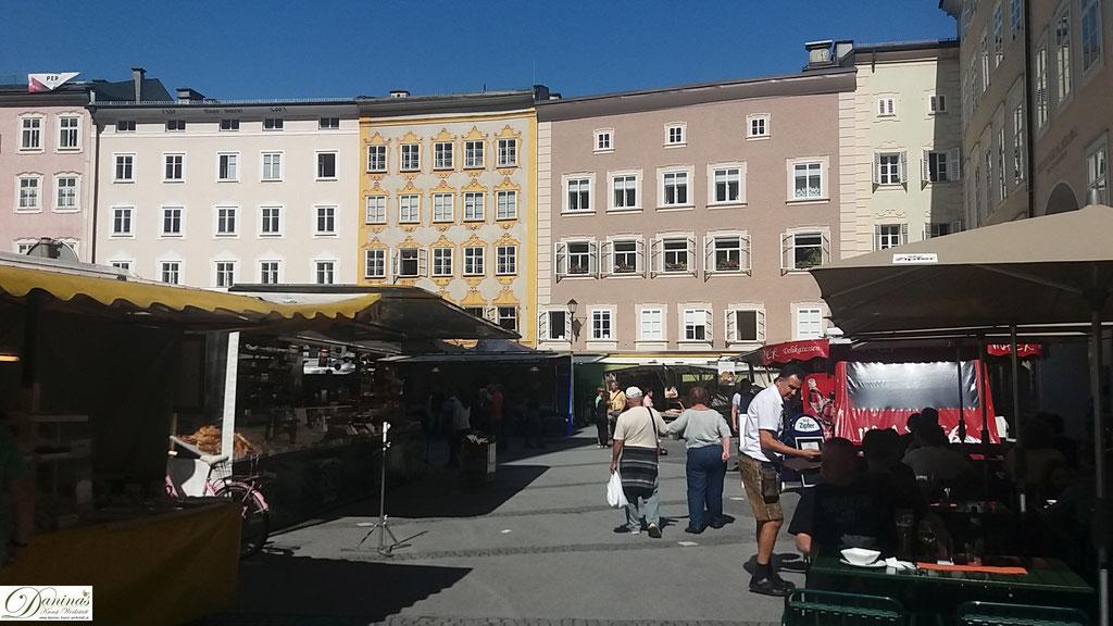 Universitätsplatz mit Grünmarkt und der Rückseite von Mozarts Geburtshaus in Gelb.