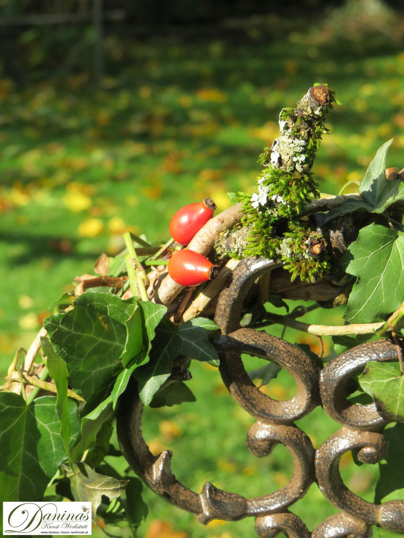 Herbstkranz mit Hagebutten und moosigem Ast