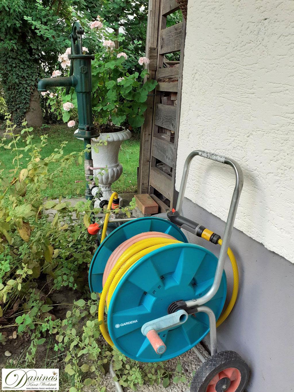 Ein Brunnen im naturnahen Garten ermöglicht das Blumengießen mit Grundwasser