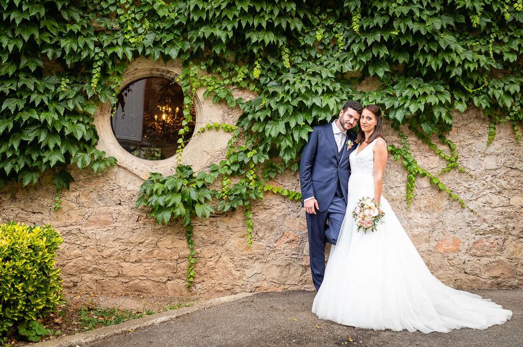 portrait de mariés devant un mur de lierre