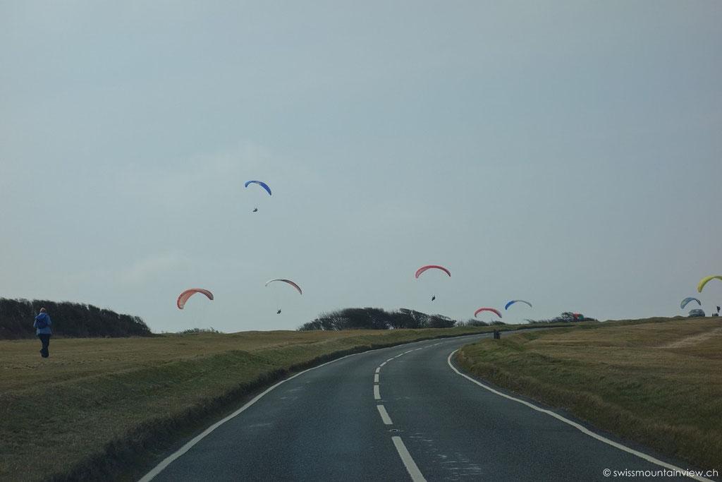 Konnte es fast nicht glauben - Paraglider, die von den Klippen hinaus aufs Meer springen...