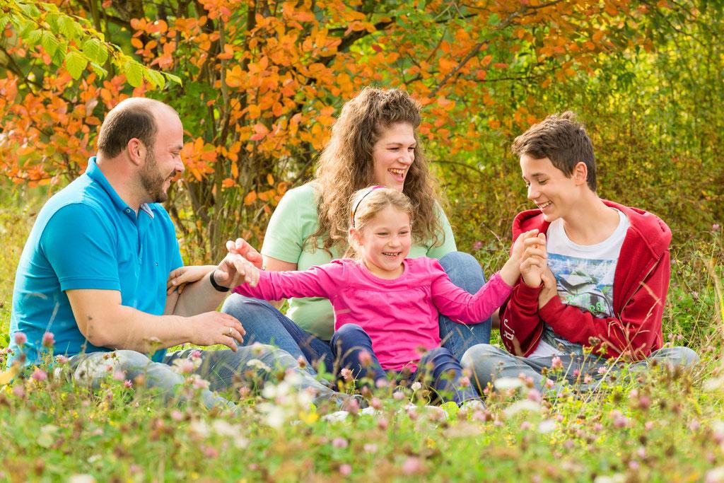 Vierköpfige Familie hat Spaß beim Familien Outdoor Shooting in der schönen Herbst Natur