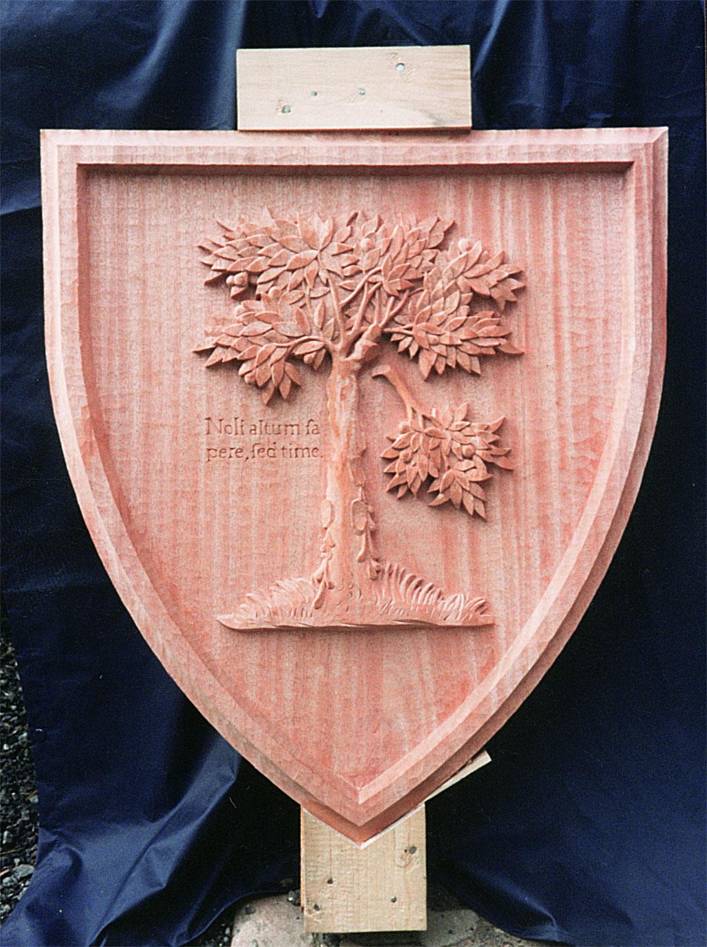 Wappenschild aus Holz geschnitzt mit einem Baum von dem ein Ast abbricht.