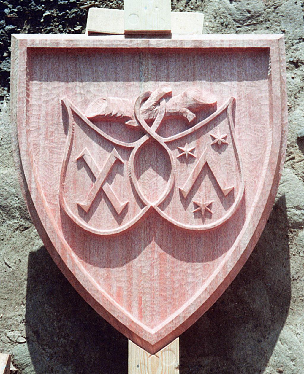 Wappenschild aus Holz geschnitzt mit dem Motiv der Druckermarke Fust und Schöffer.