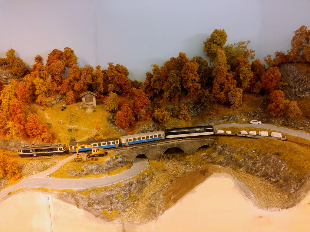 Der Regionalzug ist bestens ausgelastet. Er führt neben einem Panoramawagen zwei beladene Marmortransportwagen mit.