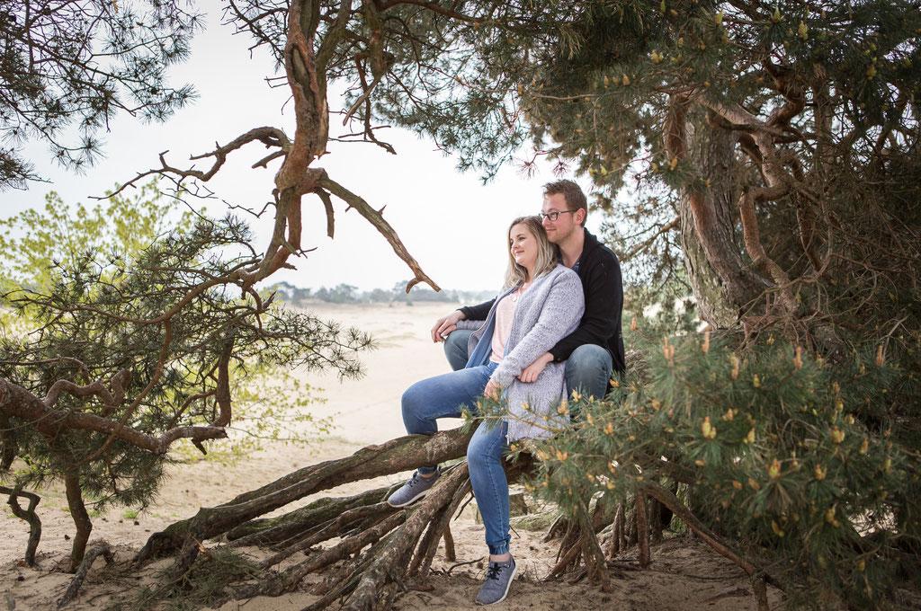Het onderwerp (de man en vrouw) zitten voor het lichtste gedeelte van de foto, de takken vormen een doorkijkje.