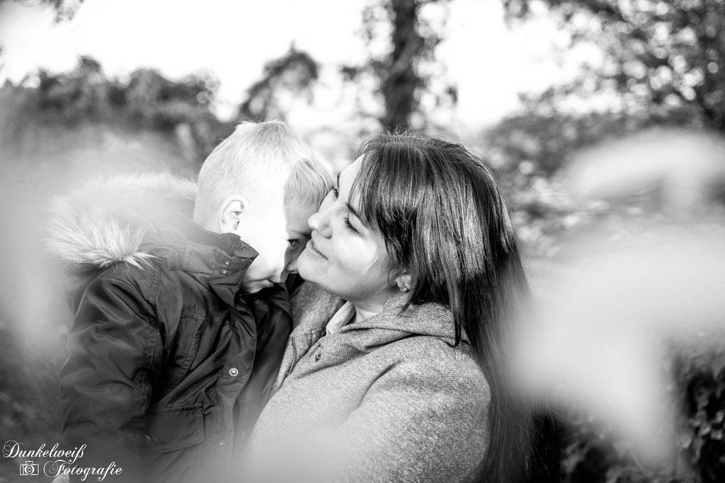 Familienfotografie -  Mutter mit Sohn auf Arm durch die Blätter fotografiert
