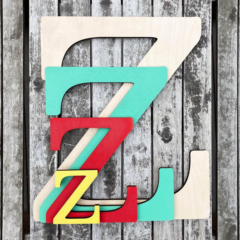 Buchstaben aus Holz in verschiedenen Farben für die Wand.