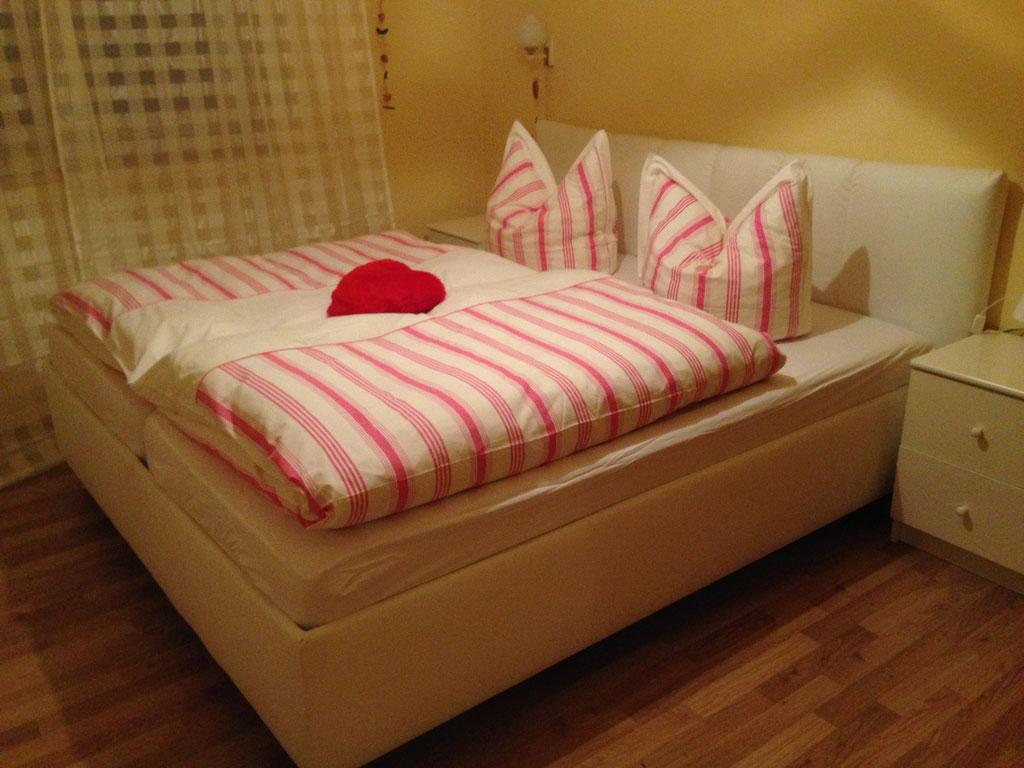 Im Schlafzimmer wartet auf Sie ein liebevoll hergerichtetes Doppelbett.