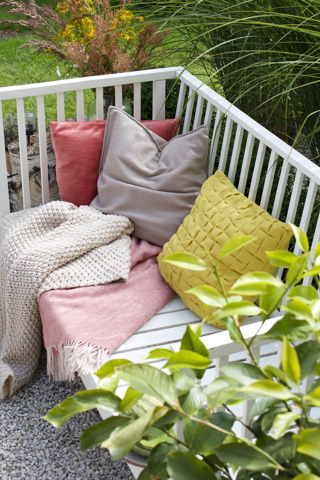 dieartigeBLOG - Weiße Gartenbank mit Kissen in Rosa und Limonengelb, Wolldecken, Kies-Terrasse