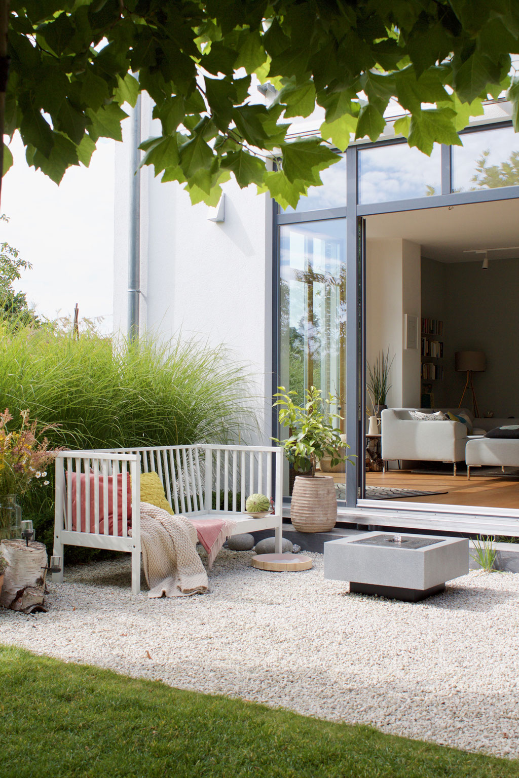 dieartigeBLOG - Weiße Gartenbank, Kies-Terrasse mit Brunnen, Wohnzimmer mit offenen Flügeltüren
