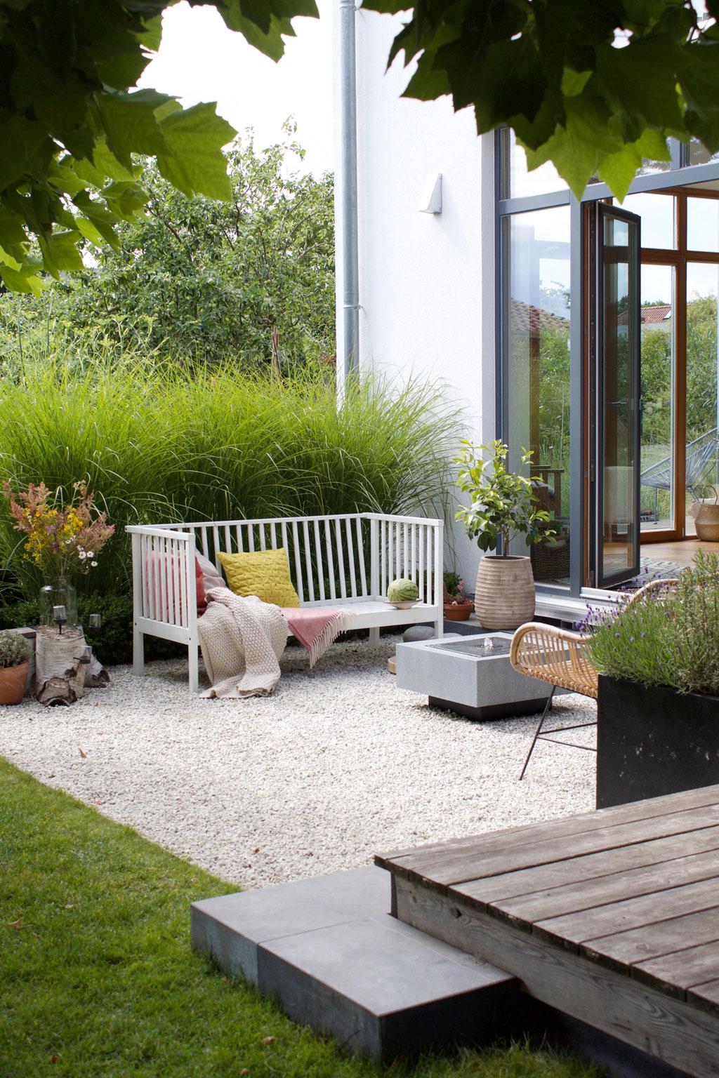 dieartigeBLOG - Gartenbank mit Kissen in Rosa und Zitronengelb, Kies-Terrasse, Gräser, Brunnen, Wiesenblumenstrauß
