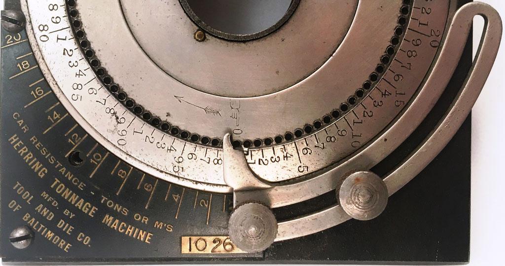 El mecanismo situado en la parte inferior del anverso sirve  para calcular las cargas de los vagones individuales de un tren y colocar en el total una asignación fija de tonelaje por vagón