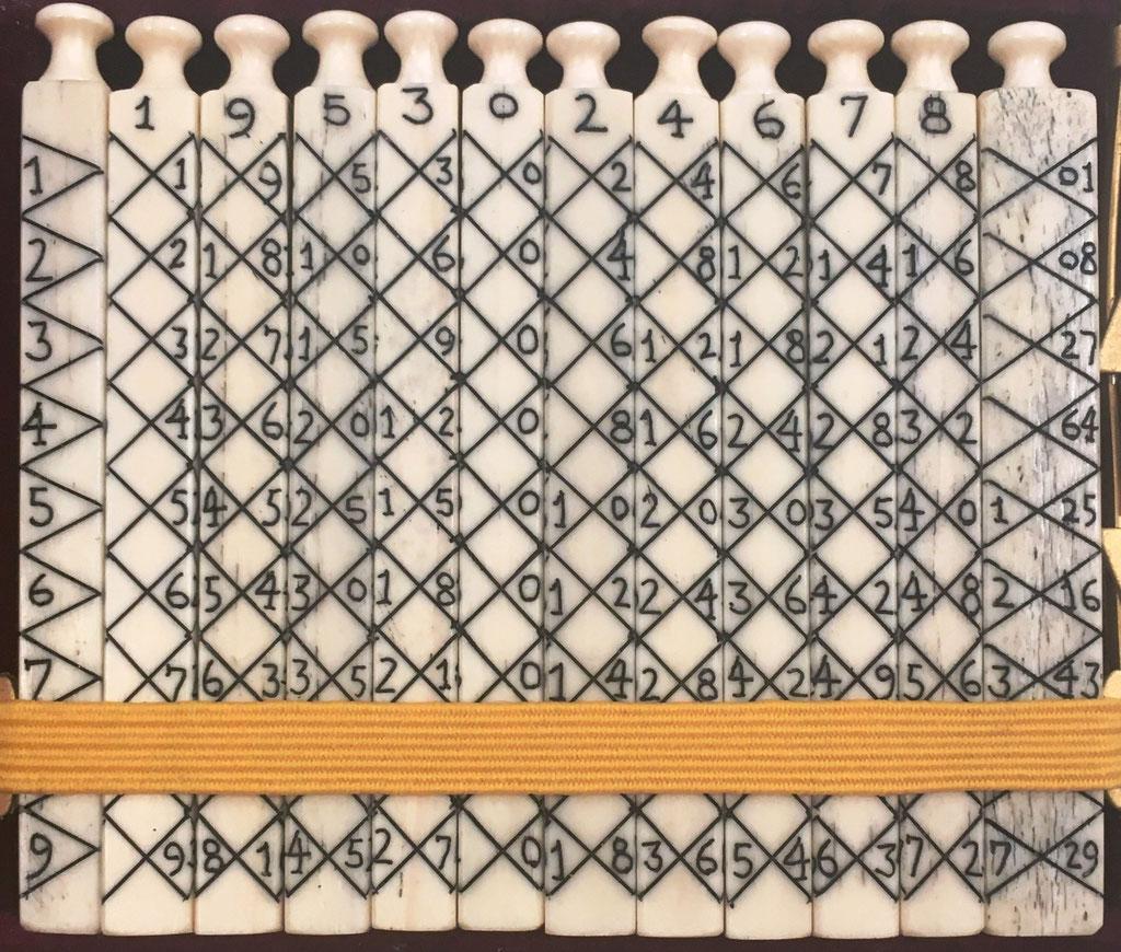 Ábaco multiplicativo de NAPIER, 12 varillas cuadrangulares (11 de 0.6x7 cm y 1 de 0.8x7 cm). Diseño: romboidal diagonal principal, ascendente hacia abajo