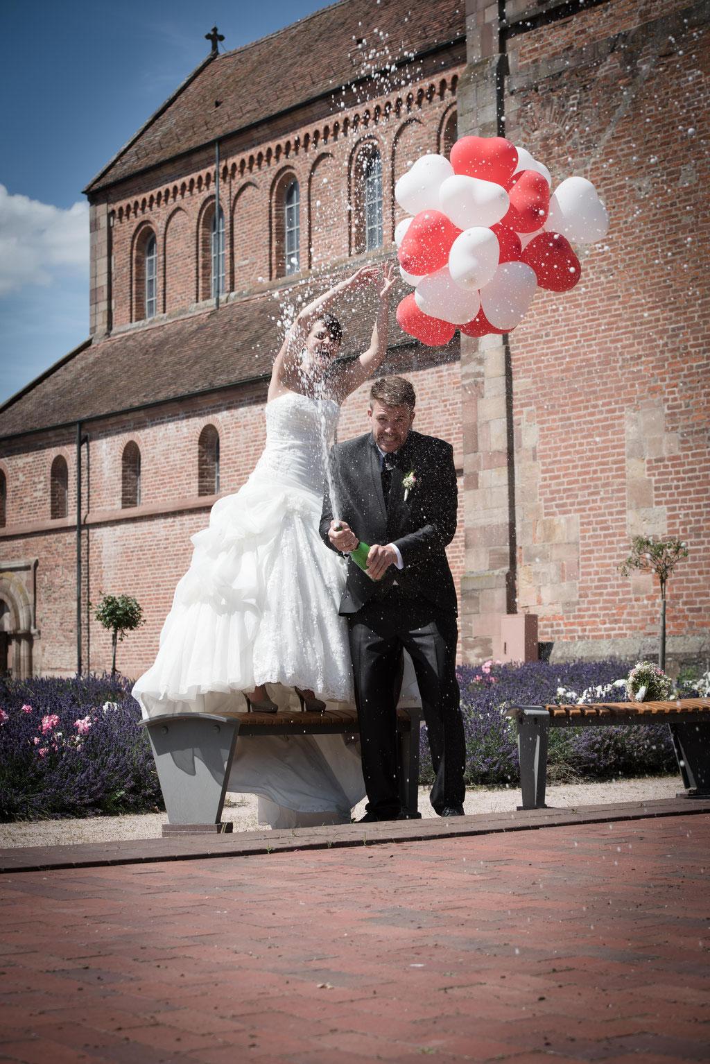 Brautpaar mit Sektflasche Schwarzacher Münster Rastet Baden-Baden / Hochzeitsfotograf Daniel Keller