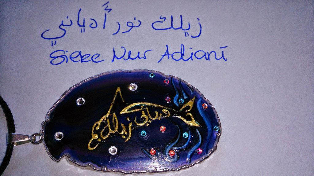 """~ Bild: Delfin-Anhänger mit arabischer Kalligrafie, Namenszug 'Silke Nur Adiani', weisser Hintergrund ~ Das """"S"""" ins """"Silke"""" wurde freikünstlerisch zu einem arabischen """"Z"""", um die Flosse des Delfins darstellen zu können."""