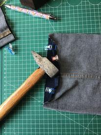 outil marteau apposé sur ourlet de pantalon jean