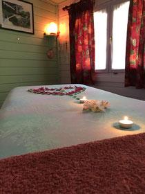 Table de massage, lampe de sel et fenêtre donnent un éclairage doux, l'ambiance est confortable et douce