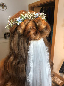 Ansicht des Hinterkopfes einer Braut mit Blumenkranz über einer Hochsteckfrisur und tief sitzendem weißen Schleier.