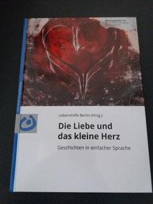 Foto vom Buch, unten weiß mit Titel: Die Liebe und das kleine Herz, oben Gemälde mit Herz