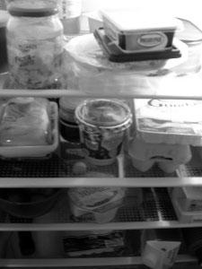 Diese Schwarzweißphotographie von Thorsten Hülsberg zeigt einen ziemlich vollen Kühlschrank.