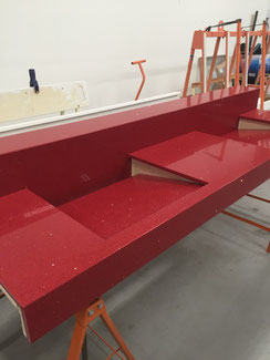Red quartz countertop with integrated sinks.