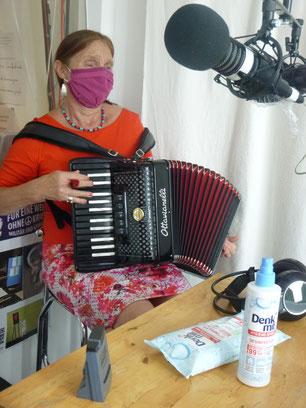 Foto: Michaela Dietl, Musikerin, live im Studio mit Akkordeon - coronabedingt verhüllt!