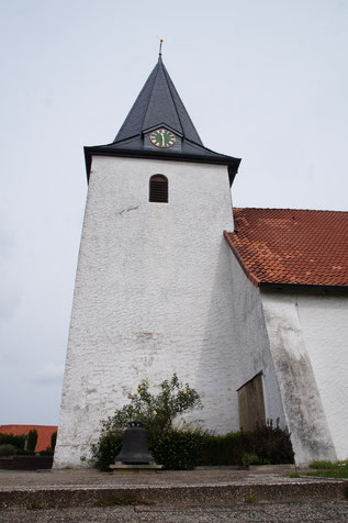 Der Turm mit weiß getünchten Wänden und dunklem spitzen Dach ragt xx Meter hoch in den Burlager Himmel.