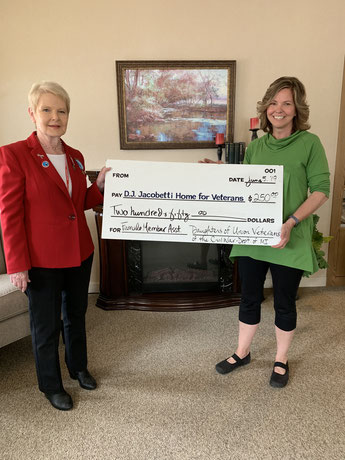 Sarah Johnson (right) receives a donation from Nancy Skerchock