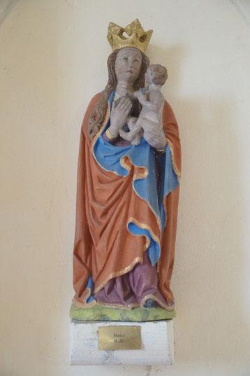 Eine gekrönte Marienstatue mit blauem und rotem Umhang mit Jesuskind auf dem Arm und dem Blick nach oben gerichtet.