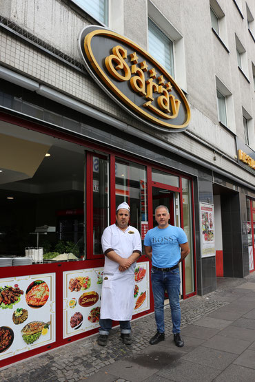 Inhaber und Koch posieren vor dem Restaurant