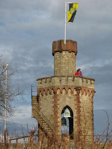 Auf die Aussichtsplattform des Flaggenturms führt eine enge Wendeltreppe. Darunter in den Spitzbögen die Glasornamente mit den vier Jahreszeiten.