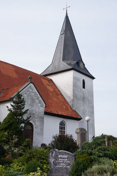 Der Turm der Burlager Marienkirche und ein Teil des Hauptschiffes sind mit ihren weißen Wänden zu sehen. Im Vordergrund sind Grabsteine und Büsche.
